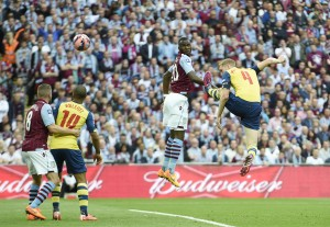 epa04776208 Arsenal's Per Mertesacker (R) scores his team's third goal against Aston Villa during the FA Cup final soccer match between Arsenal and Aston Villa at Wembley stadium in London, Britain, 30 May 2015.  EPA/FACUNDO ARRIZABALAGA DataCo terms and conditions apply. http://www.epa.eu/files/Terms%20and%20Conditions/DataCo_Terms_and_Conditions.pdf